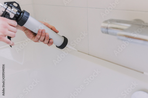 Obraz hands of man putting a silicon with a silicon tube in bathroom - fototapety do salonu