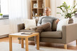 leisure and people concept - happy middle-aged man sitting on sofa at home