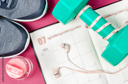 Photo  Calendar plan with green dumbbell and sneakers.