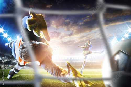Obraz Goalkeeper catches the ball on the soccer stadium - fototapety do salonu