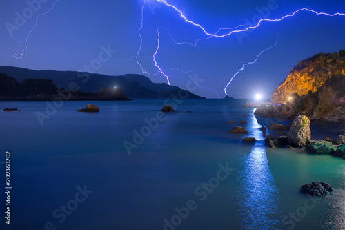 Poster  Lightning in the clear blue sky over the sea before the begins night summer storm
