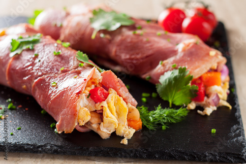 Fototapeta Rolled bacon stuffed with scrambled eggs and vegetables obraz