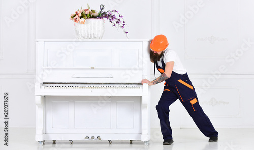 Photo Man with beard worker in helmet and overalls pushes, efforts to move piano, white background