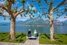 Shot Of A Senior Couple Sitting On A Bench In The Park In Villa Melzi Near Bellagio At The Famous Italian Lake Como In May