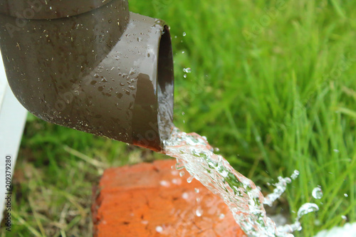 Photo A plastic drain with running water. Water jet. Close-up.