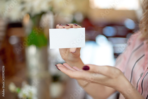Female hand with neat manicure holding white empty blank business card on beautiful blurred background with bokeh.