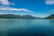 Türkiser See in Österreich mit Bergen im Hintergrund und Wolken am blauen Himmel