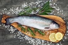 Rainbow Trout Healthy Heart Food On An Olive Wood Board, With Rosemary And Bay Leaf Herbs, Course Sea Salt And Lemon On Marble Background. High In Omega 3 Fatty Acid.