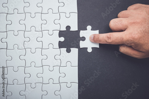 Hand holding pieces of jigsaw puzzle and insert into the missing hole Slika na platnu