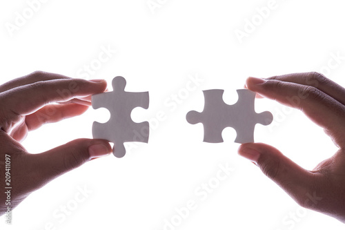 Fényképezés  Connection concept : Hands holding pieces of jigsaw puzzle on white