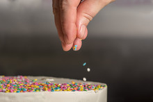 Pastry Chef Adding Sprinkles To A Birthday Cake.