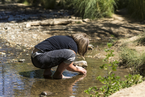 Photo  Child catching tadpoles in a rock bottomed creek