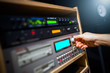 sound engineer hands adjusting professional audio recording signal processor equipment in broadcasting studio