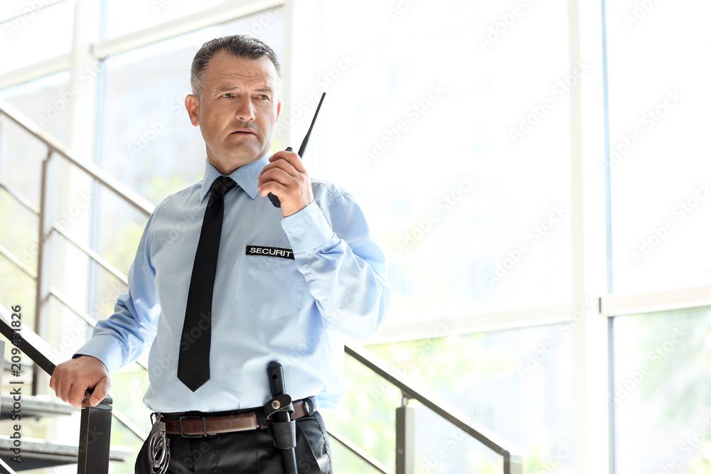 Fototapeta Male security guard using portable radio transmitter indoors