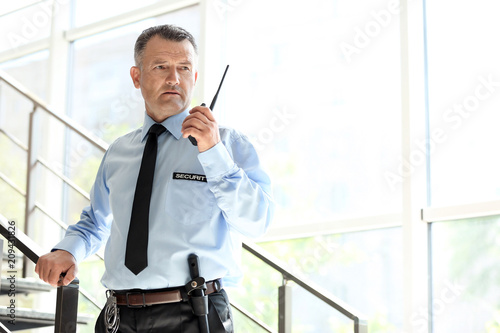 Male security guard using portable radio transmitter indoors Fototapet
