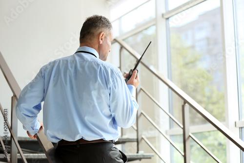 Male security guard using portable radio transmitter indoors Fototapeta