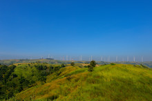 Windmills Farm Or Wind Turbine Power Generators Standing On Green Mountain Against A Blue Sky, Located Khao Kho Phetchabun Province, Thailand