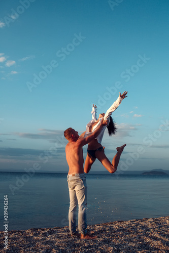 Poster Akt Couple in love dancing, having fun, sea and skyline background. Couple in love stand on beach, seashore. Honeymoon, just married concept. Man carries woman, couple happy on vacation