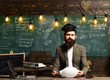 Young businessman with beard wearing suit and thinking. Blackboard background with many lightbulbs lit. Concept of doubt and choice in decision making
