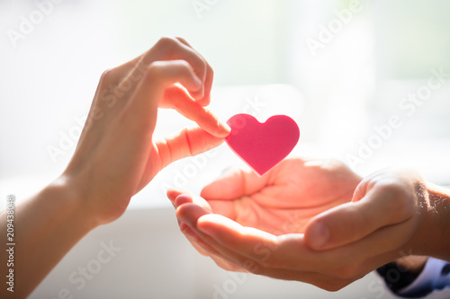 Leinwand Poster Woman Giving Heart On Man's Hand