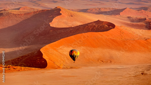 Hot air balloon in flight against orange sand dunes in Sossusvlei Namibia
