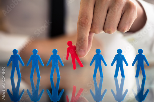 Fotografija Businessperson Picking Red Human Figures