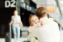 Happy Little Girl Embracing Her Dad In Airport Lounge After Arrival With Mother