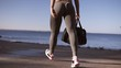 Close up woman's muscular legs, girl walks in grey legigngs with sport bag in hand. Young girl preparing to exercise or running, walking outdoor on a seaside in summer. Muscle building and slim fit