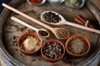 Various spices in wooden spoons and bowls and some salt on an old wooden barrel, top view, close-up, selective focus.