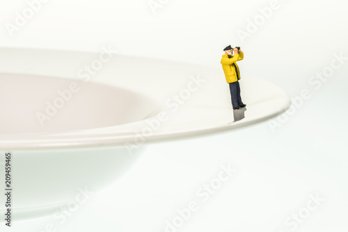Fotografie, Obraz  H0-Figur als Kapitän blickt über den Tellerrand