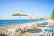 Beaches, Greece, Kos Island, Kardamena: beautiful holiday setting on a secluded beach with umbrellas on the Greek Aegean Sea with turquoise waters and a picturesque bay and islands in the background