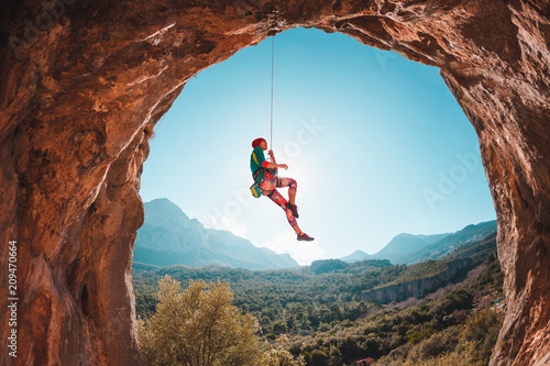 The climber is hanging on a rope. Fototapeta