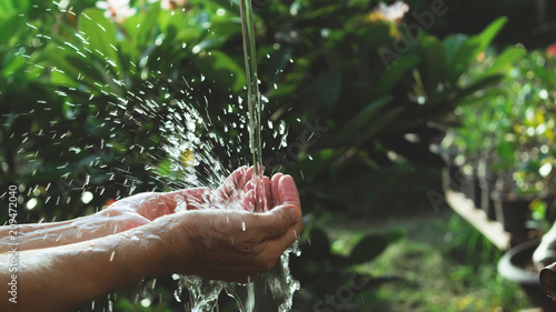Fotografie, Obraz  closeup water flow to hand of women for nature concept on the garden background