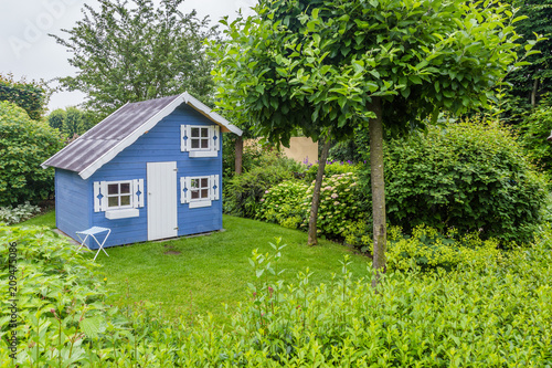 Fototapeta Cozy little blue playhouse in a green garden