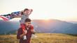 Leinwandbild Motiv happy family father and child  with flag of united states enjoying  sunset on nature.