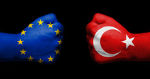 Flag Of European Union And Turkey Painted On Two Clenched Fists Facing Each Other On Black Background/European Union - Turkey Relations Concept