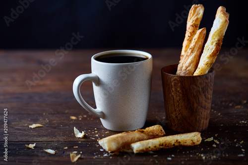 Poster Cafe Coffee cup, breadsticks and croissants on an old wooden background, close-up, selective focus.