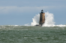 Large Wave Covers Stone Lighthouse Tower In Maine