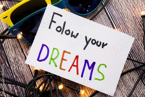 Photo  Follow your dreams motivational handwritten message on white paper above retro wooden background with lights spread in distinctive ways