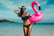 A beautiful sexy amazing young woman on the beach sits on an inflatable pink flamingo and laughs, has a great time, tanned perfect body, long hair, black bikini, fashion accessories, low key photo