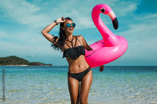 Fototapeta A beautiful sexy amazing young woman on the beach sits on an inflatable pink flamingo and laughs, has a great time, tanned perfect body, long hair, black bikini, fashion accessories, low key photo obraz