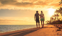 Young Couple Enjoying A Walk Down The Beach Together.