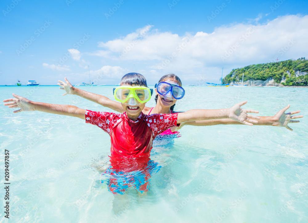 Fototapeta Two happy kids in diving masks having fun on the beach