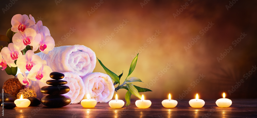 Fototapeta Spa Concept - Massage Stones With Towels And Candles In Natural Background