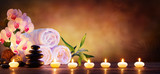 Fototapeta Flowers - Spa Concept - Massage Stones With Towels And Candles In Natural Background