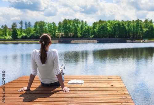 Young female sitting on edge of beautiful lake enjoying the view.