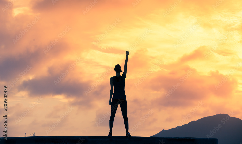 Fototapeta Stand strong. Woman with fist in the air. Feeling motivated, strength and courage concept.