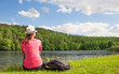 Young woman relaxed sitting next to lake on a beautiful summer day. Location Czech republic (Europe)