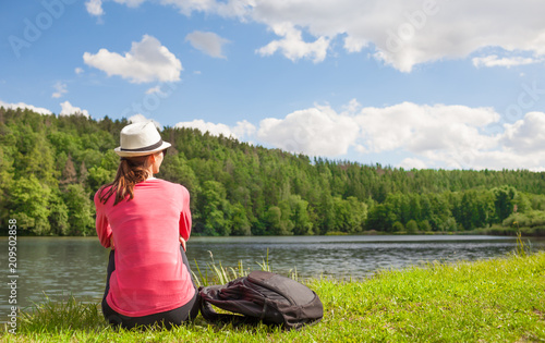 Staande foto Ontspanning Young woman relaxed sitting next to lake on a beautiful summer day. Location Czech republic (Europe)