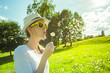 Young female blowing dandelion flower in a beautiful summer green setting.